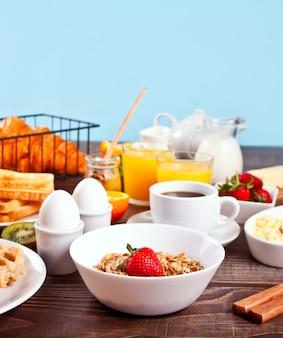 Müsli mit frischen beeren, tasse kaffee, eiern, toast auf dem tisch