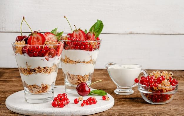 Müsli mit frischen johannisbeeren, kirschen, erdbeeren und joghurt auf holzfläche, kopierfläche.