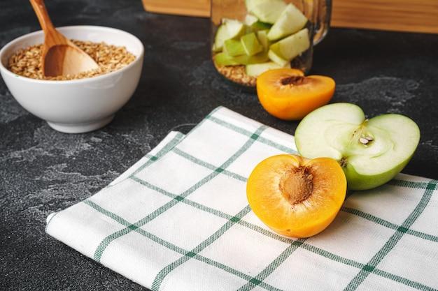 Müsli mit geschnittenen früchten in glas auf karierter serviette