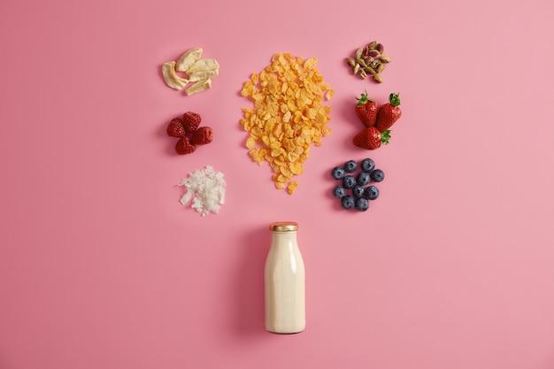 Müsli mit getrockneten äpfeln, datteln, cashewnüssen, pistazien um die flasche mit milch