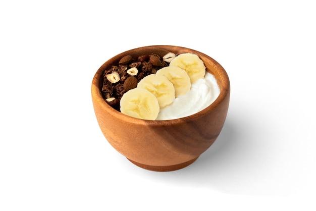 Müsli mit joghurt, banane und nüssen isoliert auf weißer oberfläche