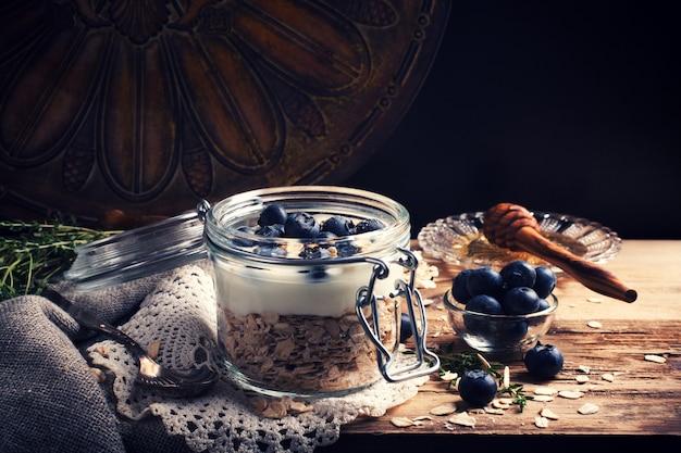 Müsli mit joghurt und blauen beeren im glas.