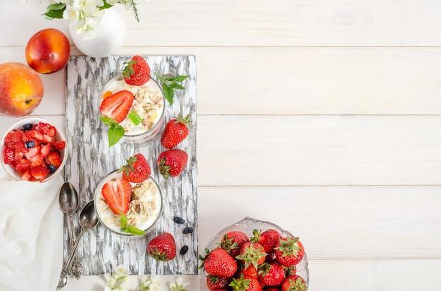 Müsli mit joghurt und frischen erdbeeren auf einem weißen hölzernen hintergrund mit kopienraum. draufsicht, flach liegen