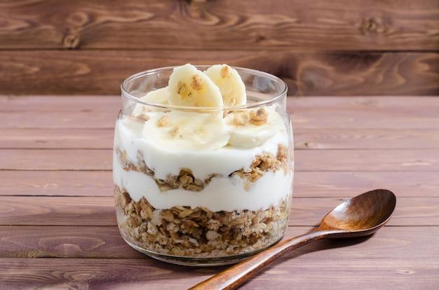 Müsli mit naturjoghurt, banane, nüssen und trockenfrüchten im glas