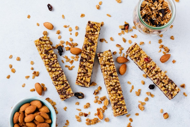 Müsli-müsliriegel mit nüssen, früchten und beeren auf weißem steintisch. müsliriegel. gesunder snack. ansicht von oben.