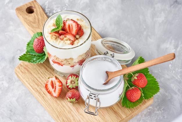 Müsli oder joghurt mit erdbeere im glas, frischen beeren und glas mit zucker auf einem schneidebrett, draufsicht