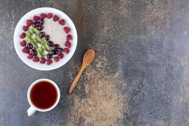 Müsli-porridge mit himbeeren und einer tasse getränk
