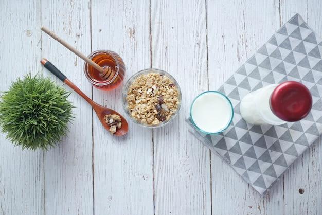 Müslifrühstück in schüsselbrot und honig auf weißem hintergrund