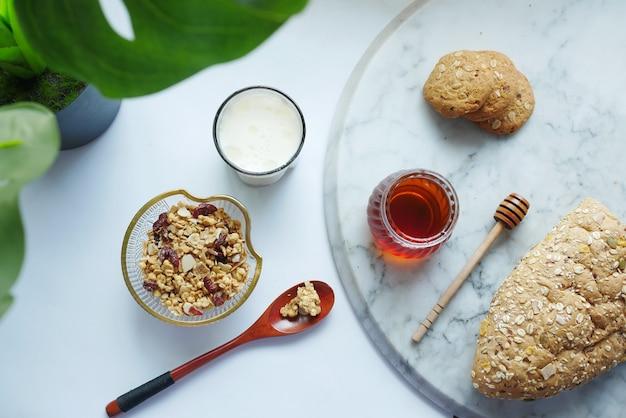 Müslifrühstück in schüsselbrot und honig auf weißer fläche