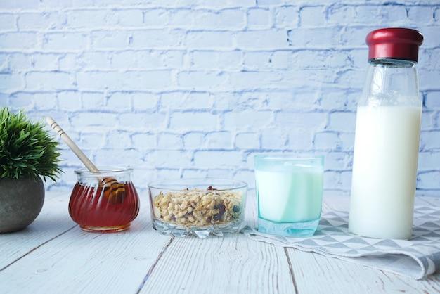 Müslifrühstück in schüsselmilch und honig auf holztischoberfläche