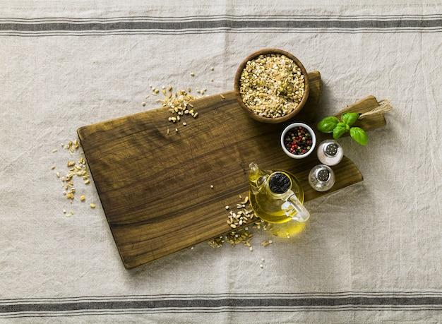 Müslimischung in einer holzschale auf einem schneidebrett mit olivenöl, bunten paprika und gewürzen. hausmannskost auf leinentischdecke