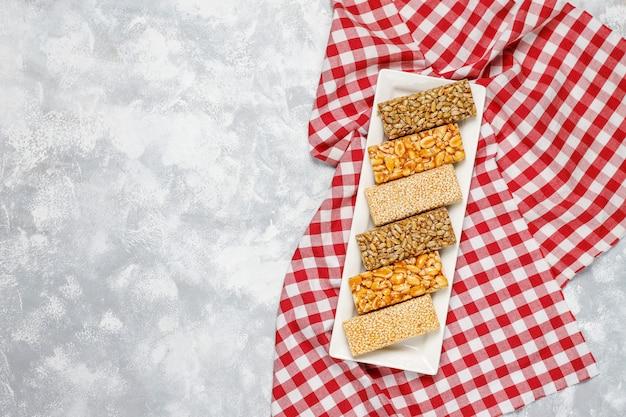 Müsliriegel. gesunder süßer nachtischsnack. sesam, erdnuss, sonnenblume in honig. gozinaki ist ein georgisches nationalgericht, orientalisch süß. draufsicht auf beton