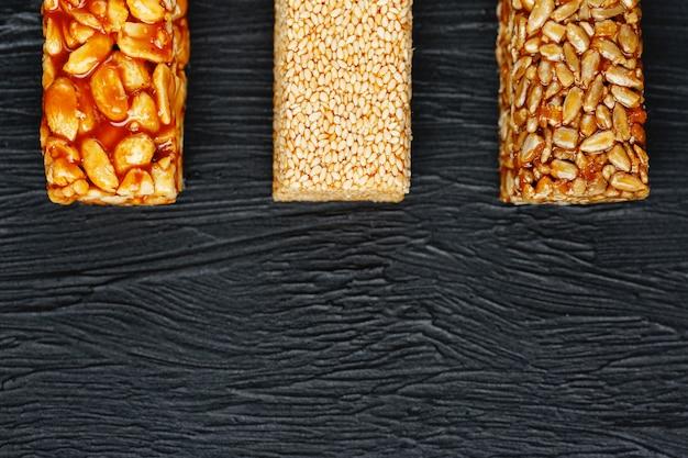 Müsliriegel mit erdnüssen, indischem sesam und sonnenblumensamen auf einem schneidebrett auf einer dunklen steintabelle. von oben betrachten. drei verschiedene bars
