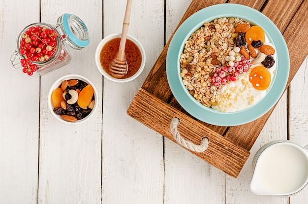 Müslischale mit getrockneten früchten, honig, milch, nüssen und frischen roten johannisbeeren auf weißem holz