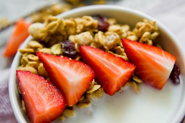 Müslischale mit müsli, erdbeeren und joghurt.
