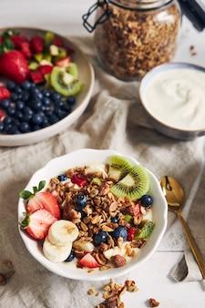 Müslischalen mit joghurt, früchten und beeren auf weißer oberfläche