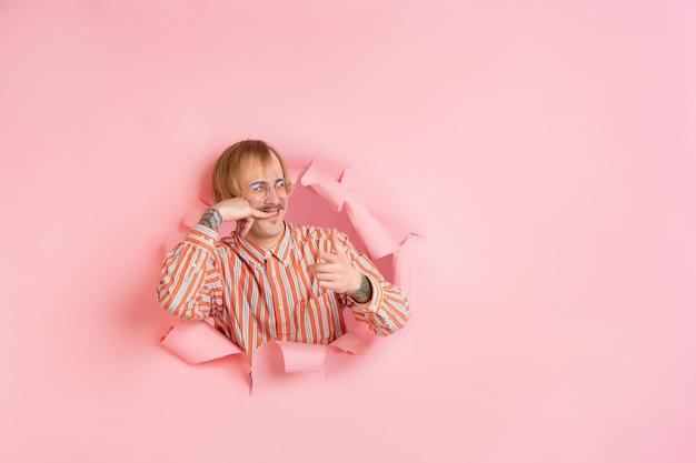 Müssen sie mich anrufen? fröhlicher kaukasischer junger mann posiert in zerrissenem korallenpapier, emotional ausdrucksstark.
