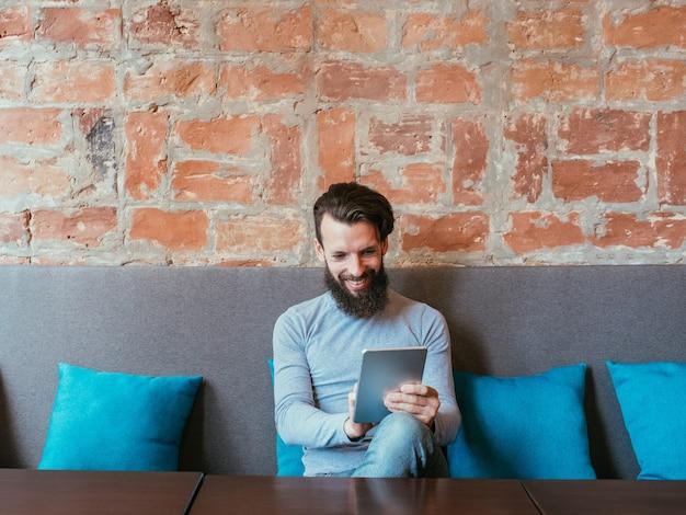 Müßige freizeit und internetabhängigkeit. mann, der lächelt, während er tablette benutzt
