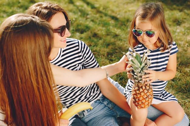 Mütter mit den kindern, die in einem sommerpark spielen