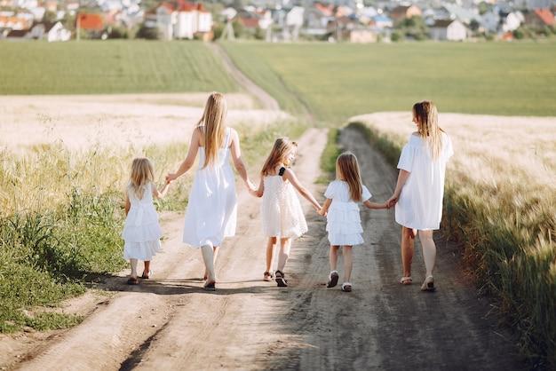 Mütter mit den töchtern, die auf einem herbstgebiet spielen