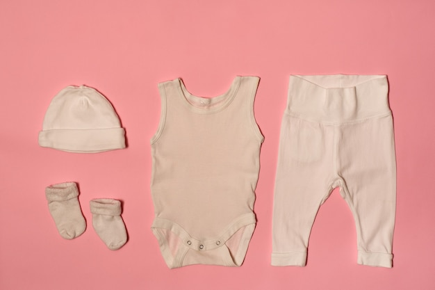 Mütze, body, hose und socken auf rosa oberfläche