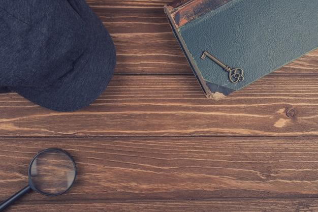 Mütze eines detektivs, einer lupe und eines alten buches