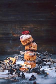 Muffin mit johannisbeeren auf dunklem hintergrund. muffins ausgekleideter turm, um entlang der rauchoberfläche zu reisen. fabelhaftes konzept