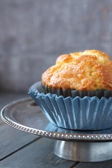 Muffin mit rosinen in den blauen verpackungen auf einer metallplatte
