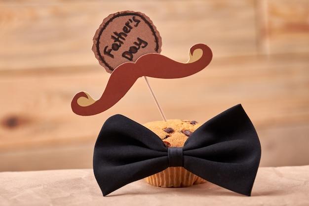 Muffin mit schnurrbart. grußkarte und fliege. leckeres geschenk für papa.