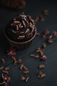 Muffin oder cupcake mit schokoladenförmiger creme am schwarzen tisch. flatlay draufsicht.