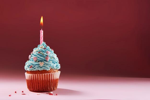 Muffin oder ein kleiner kuchen mit einer brennenden kerze. konzept der glückwünsche, urlaub.