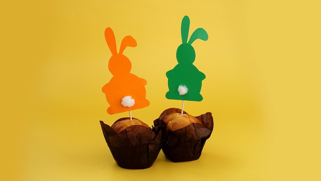 Muffin verziert mit einem papierkaninchen auf einem zahnstocher. osterdeko für cupcakes. festliche süßigkeiten und gebäck. gelber hintergrund