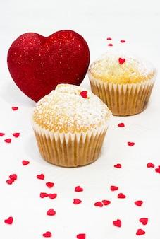 Muffinformen aus papier, bestreut mit puderzucker, rot glänzendem herz und vielen kleinen zuckerherzen auf einem weißen