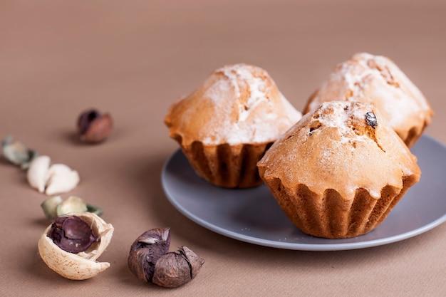 Muffinkuchen auf einem grauen teller. beige - kaffeehintergrund.