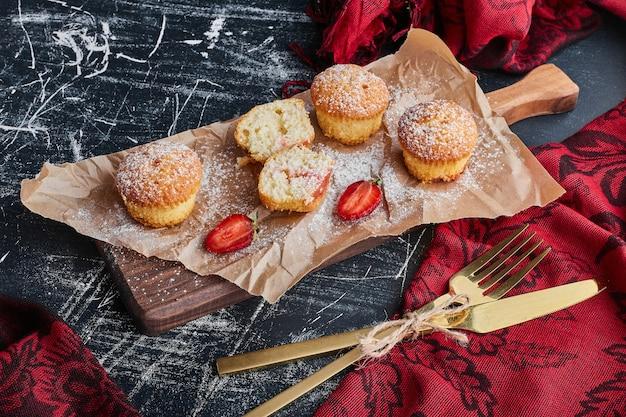 Muffins auf einem holzbrett mit besteck herum.