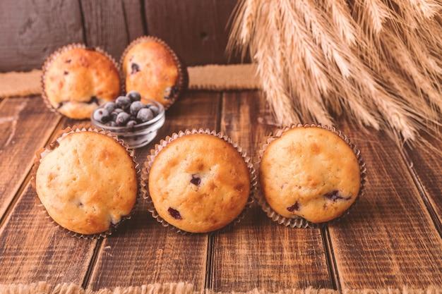 Muffins auf hölzernem auf rustikaler art. cupcake mit johannisbeeren.