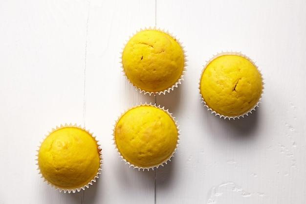 Muffins auf weißem tisch, flach liegen. cupcakes auf hölzernem hintergrund, draufsicht. hausgemachte bäckerei