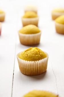 Muffins auf weißem tisch, nahaufnahme, selektiver fokus. gekochter kürbis oder orange cupcakes auf hölzernem hintergrund. hausgemachte bäckerei
