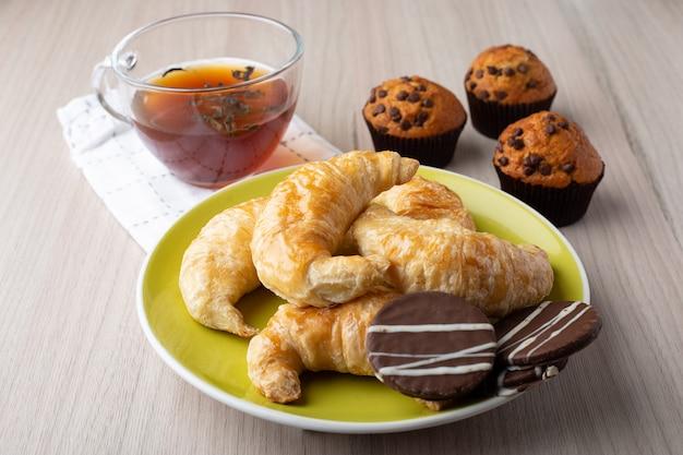 Muffins, eine tasse tee, croissants und karamellplätzchen