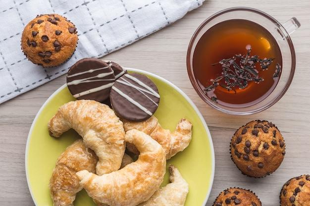 Muffins, eine tasse tee, zimt, croissants und karamellplätzchen