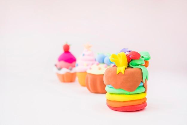 Muffins gemacht mit buntem lehm auf rosa hintergrund