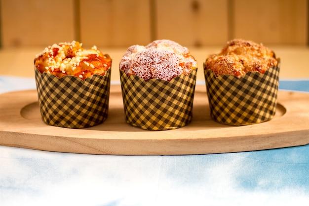 Muffins im hölzernen teller und in der tabelle mit hölzernem hintergrund