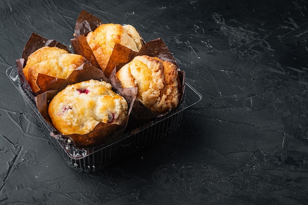 Muffins in plastik, behälterbox, auf schwarzem tisch