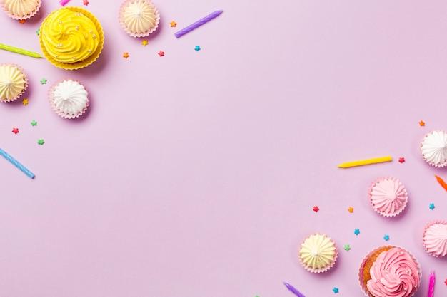Muffins; kerzen; aalaw und streusel an der ecke von rosa hintergrund