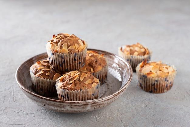 Muffins mit dem hüttenkäse verziert mit mandelflocken in einer keramischen platte.