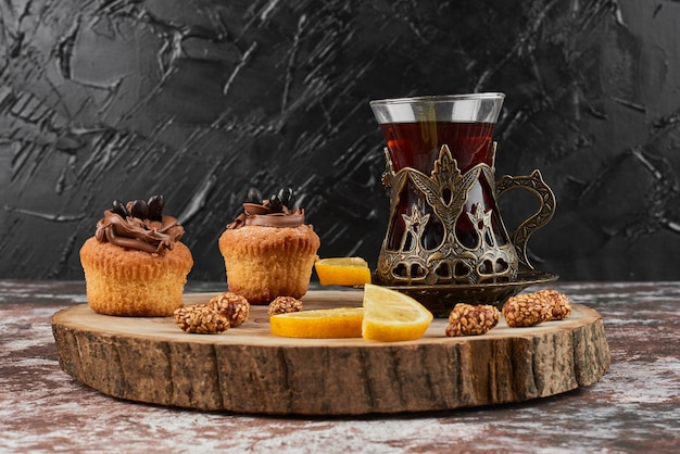 Muffins mit getränk auf einem holzbrett.