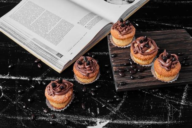 Muffins mit kakaocreme auf einem holzbrett.