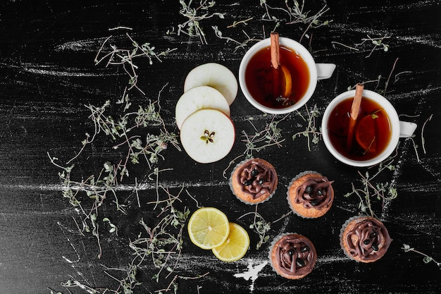 Muffins mit kakaocreme auf einer tafel mit tee.