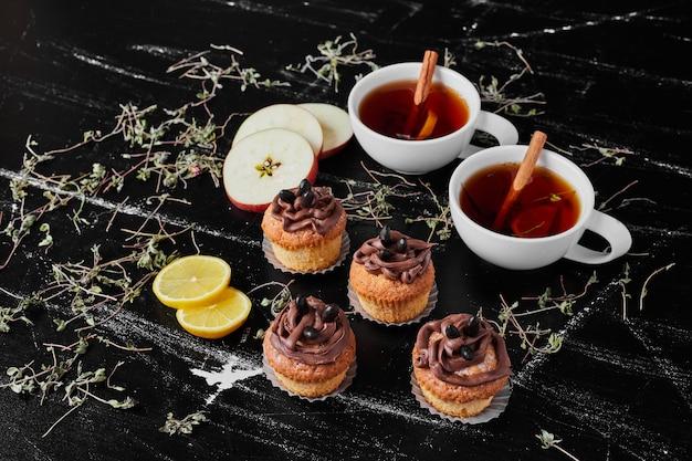 Muffins mit kakaocreme und tassen tee.