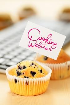 Muffins mit koch-webinar-schild auf dem holztisch